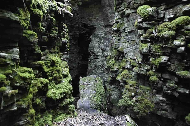 Dark shadows beyond the narrow entrance to Woodford Crevice which is part of the Bruce Trail in the Sydenham Section west of Meaford Ontario