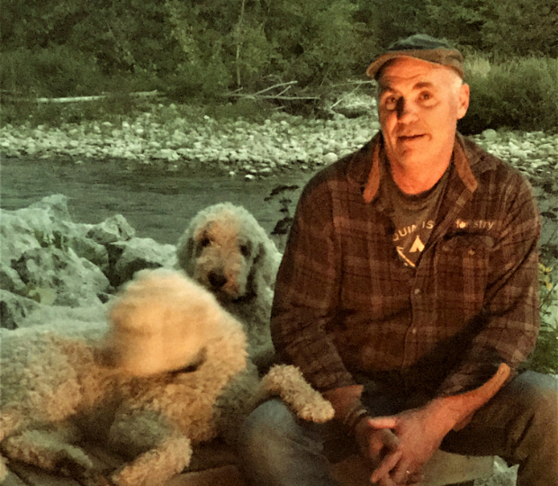 Photo Brendan Thomson seated outside with his dogs.